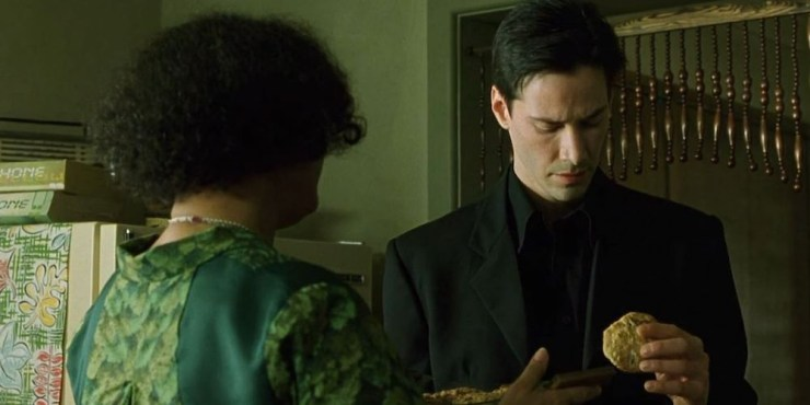 The Oracle (Gloria Foster) gives Neo (Keanu Reeves) a cookie in The Matrix