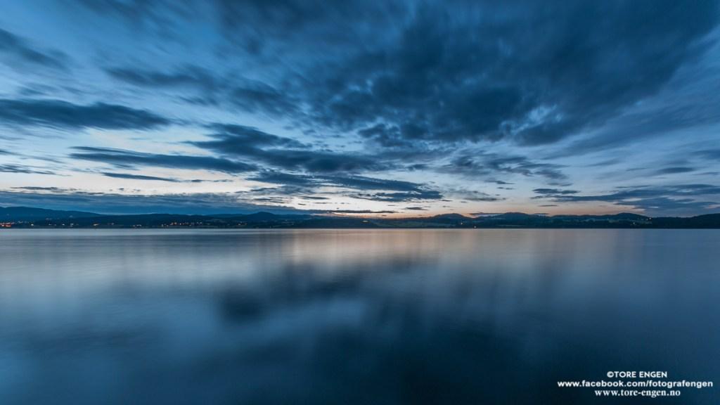 Bilde av skyer som beveger seg over stille vann på Mjøsa