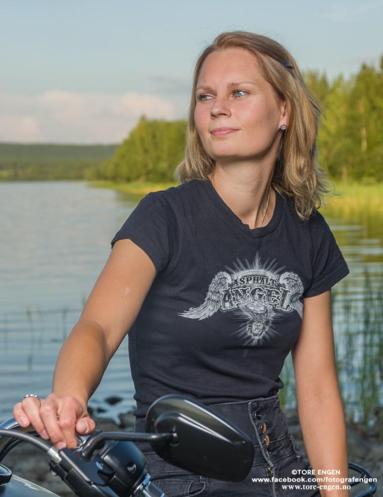 Portrett av dame sittende på sin motorsykkel i kveldssol