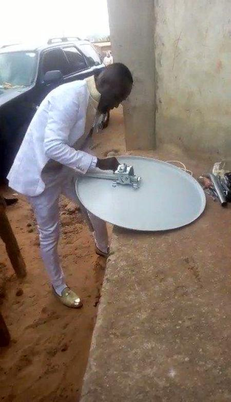 The groom fixing Dstv for a customer on his wedding day