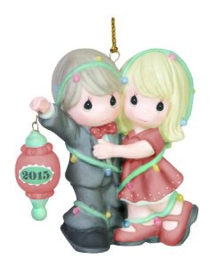 A Precious Moments Christmas Ornament featuring two people. One holds out a Christmas ornament reading 2015, while the other figure gives the first a hug.