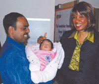 Proud poppa Sivakanthan Kandiah, left, holds Pranavi, the first baby born at the new Birthing and Newborn Centre at Centenary Hospital. Health Promotion Minister Margarett Best, right, helped celebrate the birthdays of both Pranavi and the Newborn Centre in December. (Courtesy Centenary Hospital)