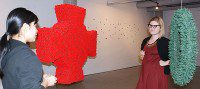 Jackie Tan, an exhibitions assistant, and Katrina Enros, a gallery administrator, take a look at a piece titled Hugs and Kisses by Anitra Hamilton. (Selena Mann/Toronto Observer)