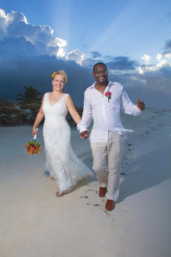 wedding photo of couple walking on beach with dramatic sky