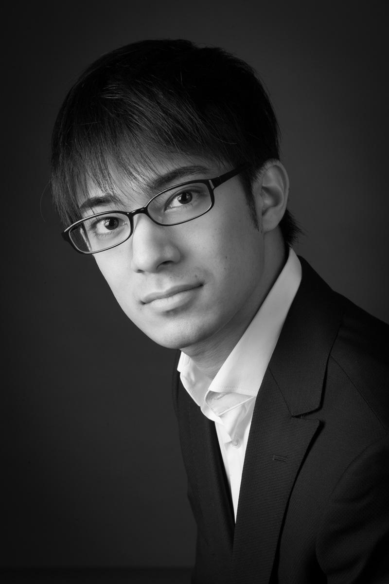 B+W LinkedIn headshot of man with glasses in portrait studio