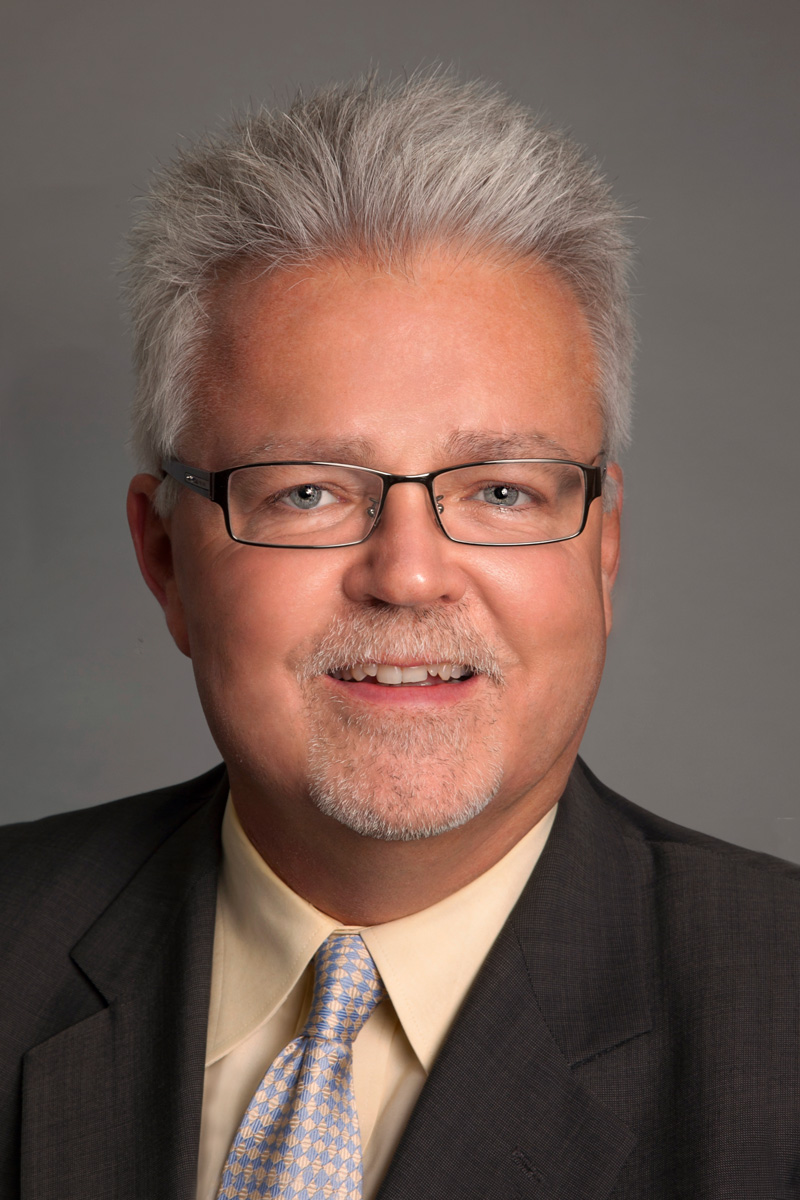 Corporate portrait of man with suit and grey background taken in Toronto portrait studio