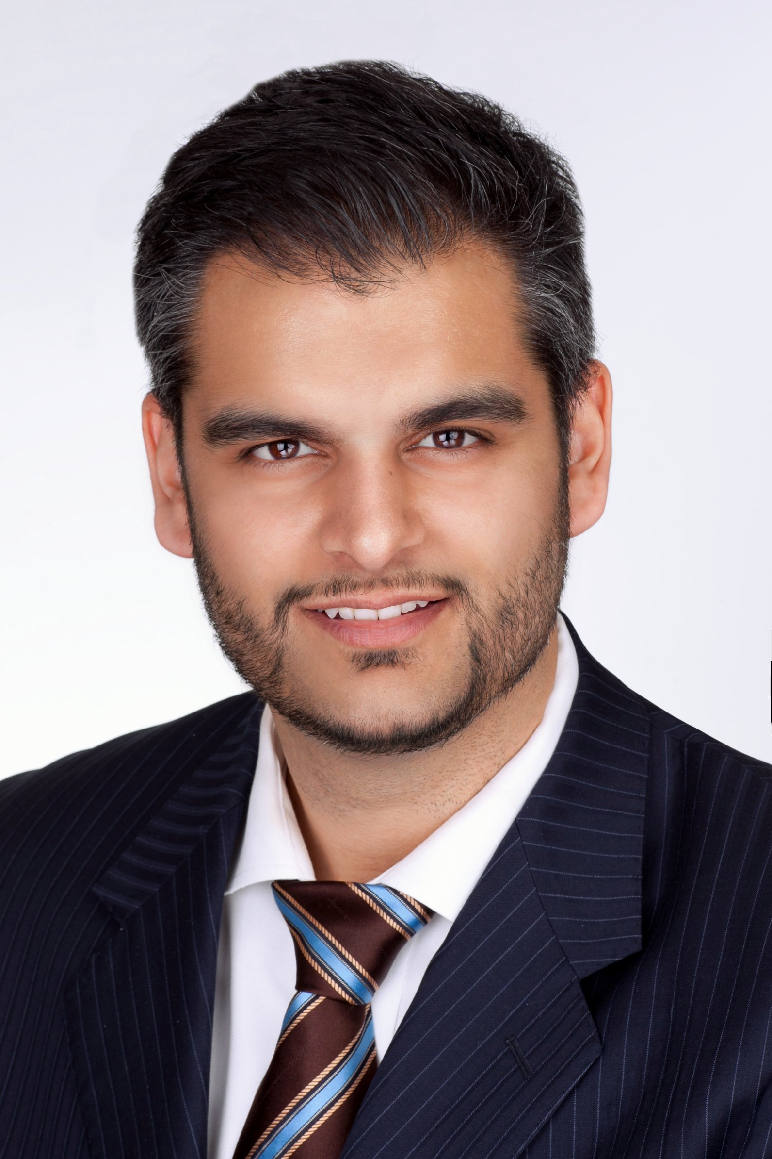 Professional headshot of man with suit and with a white background