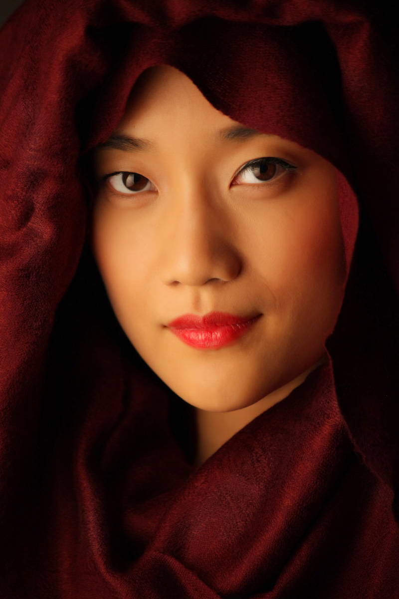 Asian women portrait with red scarp around head and face with warm tones taken in studio