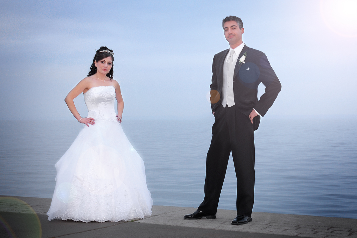 Wedding photo of bride and groom standing in front of lake