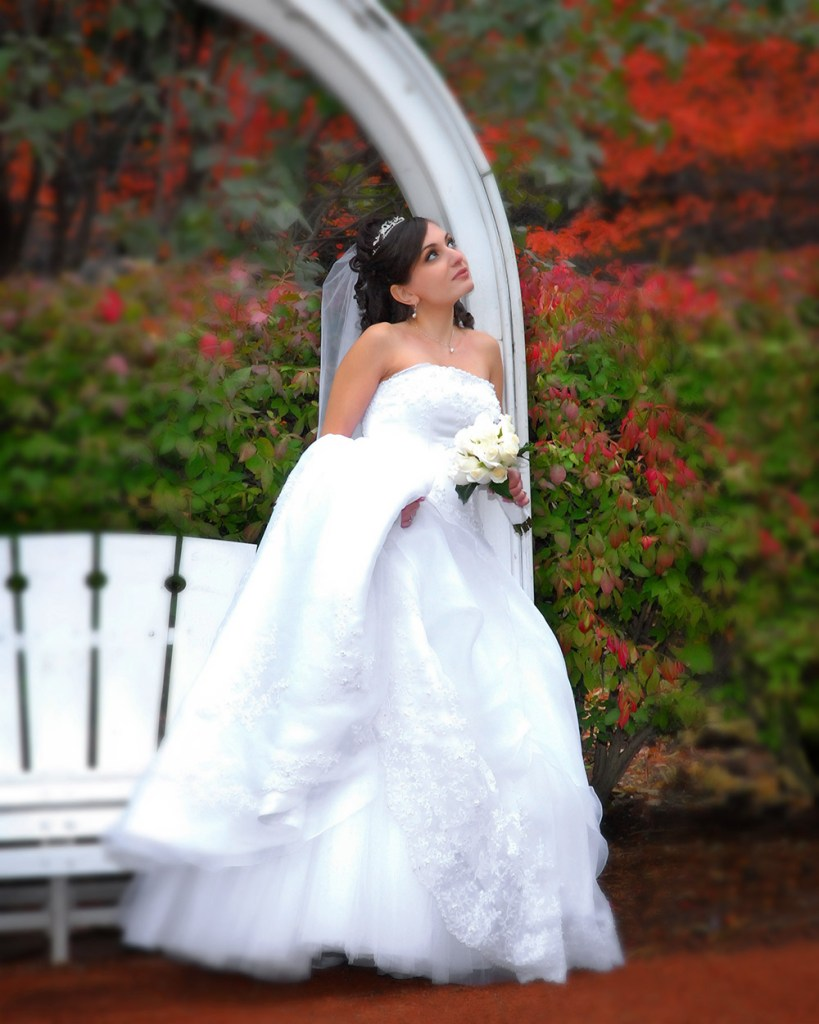 Wedding photo of bride leaning against a arch way with flowers in the background