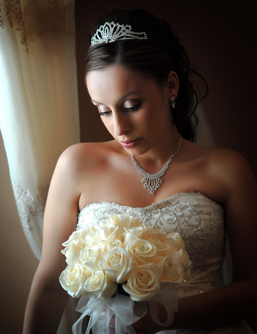 Bride looking down at flowers next to a window