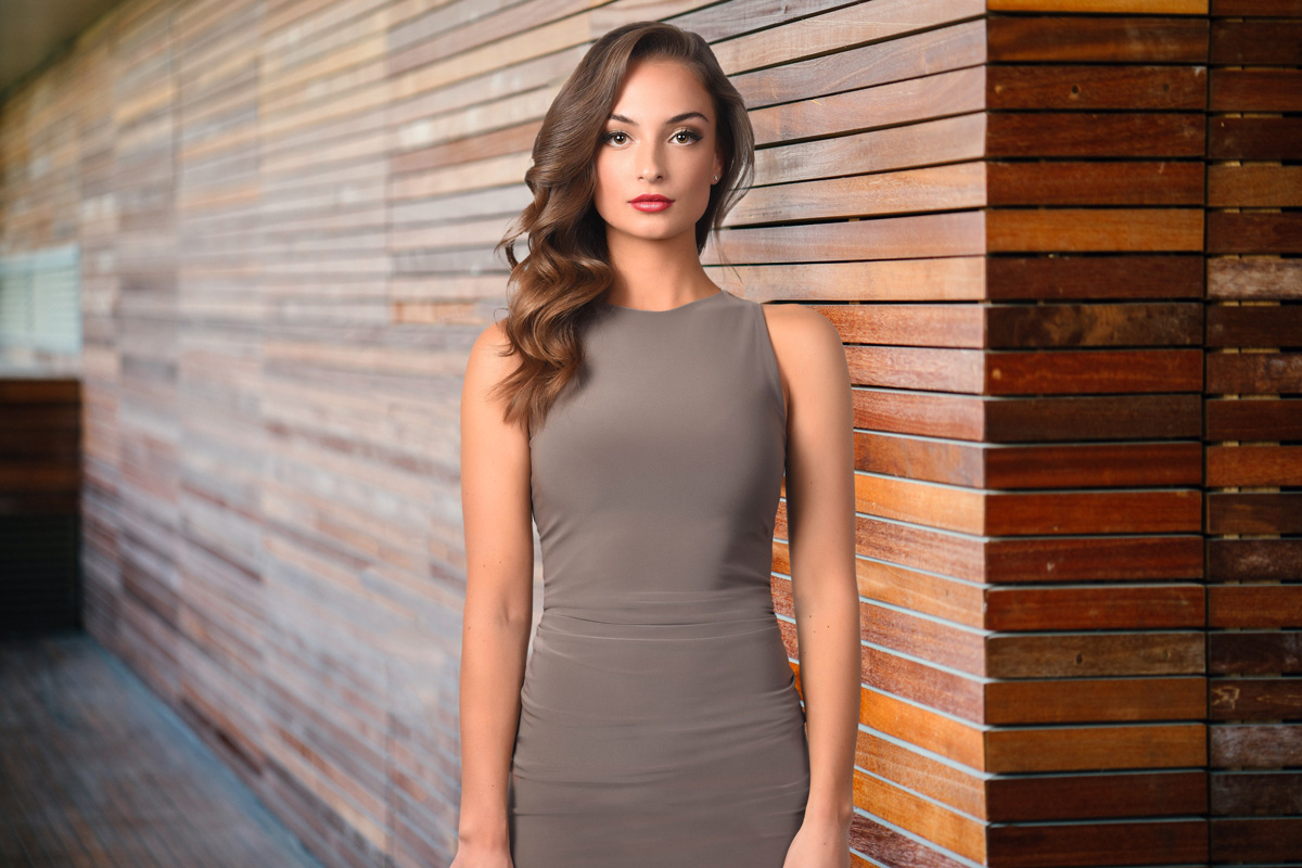 Corporate business portrait of girl standing with grey dress with wood background