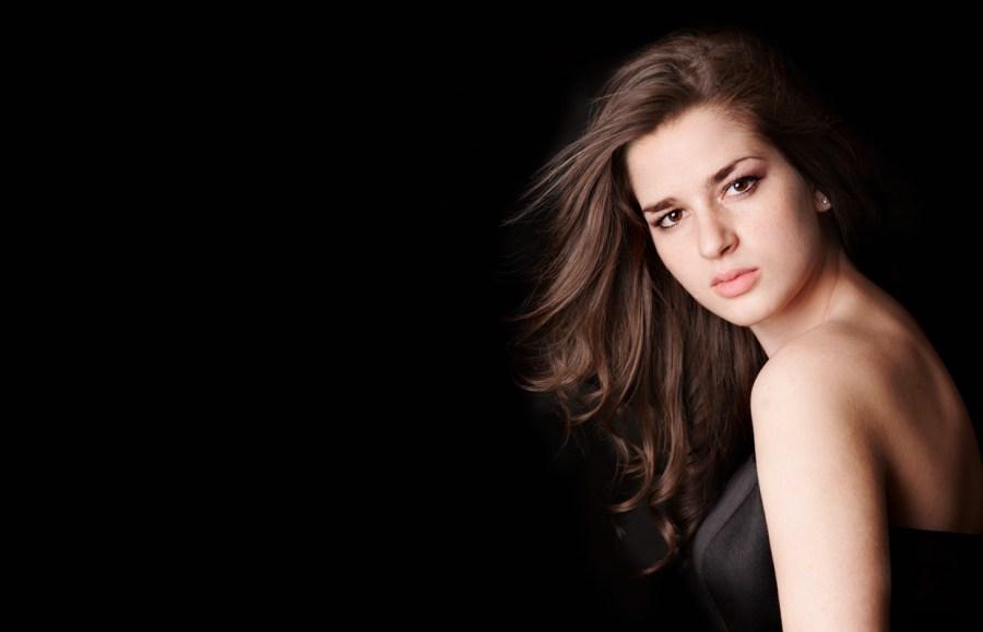 Model portfolio portrait of women with dark hair against black background