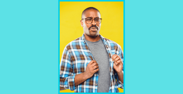 A photo of Brian Mitchell looking towards the camera, against a yellow background. He wears glasses, has short hair and a moustache, and wears a grey shirt under a blue plaid button up.