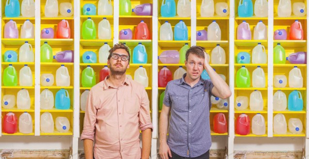 Image features Tom Hill and Devin Mackenzie of Hip.Bang!, two early-30's comedians, looking stressed, standing in front of a massive wall of brightly coloured four-litre jugs of water, which seem to stretch metres and metres above them.