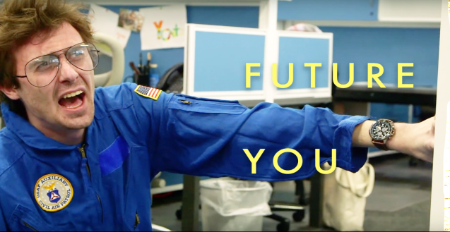 "A man in despair braces himself against an office desk. He dons a blue NASA jumpsuit and a large traditional watch on his wrist. The title text sandwiches the outstretched arm reading, ""Future You""."