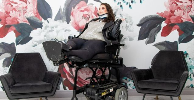 Ophira, a white disabled femme presenting person with long curly hair, smiling slightly at the camera, in front of a wall painted with large pink, white, grey and blue flowers, elevated in their power wheelchair above two chairs on either side, tilted back with legs raised in a reclining position, wearing a silver sparkly shirt and a black leather jacket.