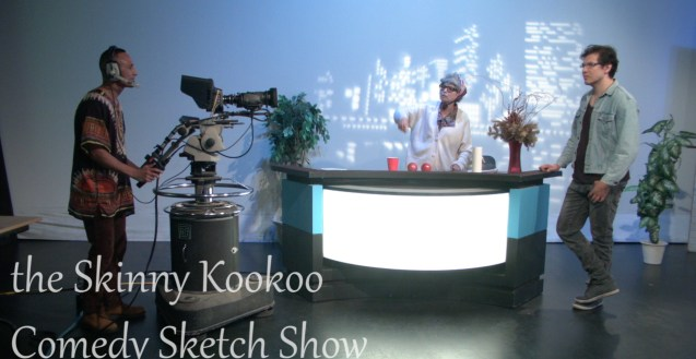 On set of the Skinny Kookoo Comedy Sketch Show. Skinny Kookoo stands behind a news desk with her grandson on the left side and Aqqalu Meekis on the right. A TV camera operator points the camera at them to capture the footage