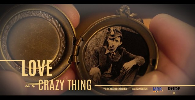 """A graphic that shows an antique Love Locket with a black and white photo of a man who is a miner being held in the hands of a person. Along the bottom is yellow text that reads """"Love Is A Crazy Thing. Written by Mike Mildon and Luke Mitchell. Starring Lesley Robertson"""" Then two logos that read MRR 2020 and RODE."""