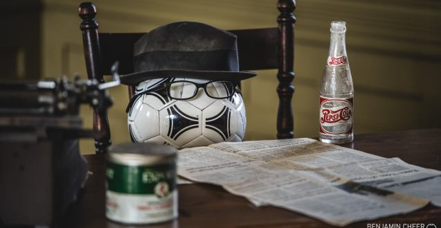 """The star of """"Balls!"""" hard at work. A black and white sports ball is seated at a table wearing a hat and glasses, with a newspaper, typewriter and bottle of pop in front of them."""