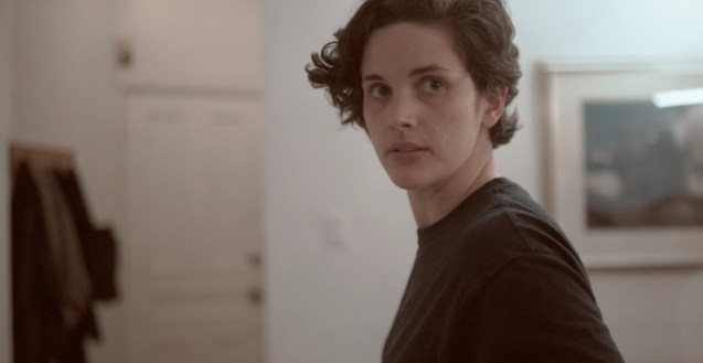Image of a young woman with short hair standing in an apartment looking over her shoulder at something beyond the camera.