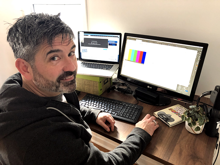 Paul sits at his desk in his home office with two screens in front of him. He is turned around to smile at the camera.