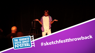 "Ajahnis Charley performing on stage wearing a brown wig and glasses, hands up as if shrugging. TOsketchfest logo and text on image that says ""#SketchFestThrowBack"""