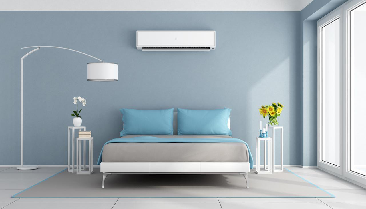A wall mounted air conditioning unit installed in a bedroom.