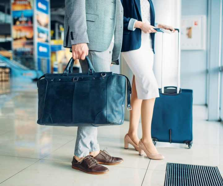 Male and female passengers with luggage in airport, business trip. Businessman and businesswoman in air terminal, negotiation travel