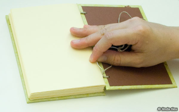 Tying knot to finish sewing book
