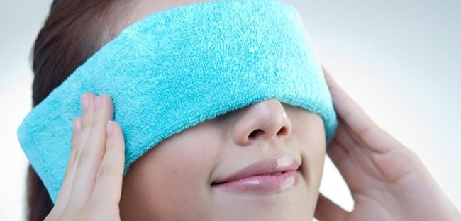 woman holding compress on her eyes