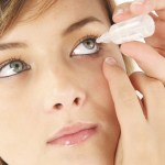 Pretty woman putting artificial tears in her eyes