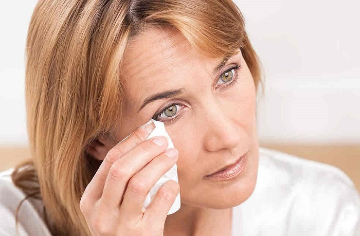 woman cleaning her eye with a tissue
