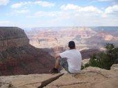Sitzend am Abgrund des Grand Canyons fällt der Blick in eine 2 km tiefe Schlucht ins rießige Tal