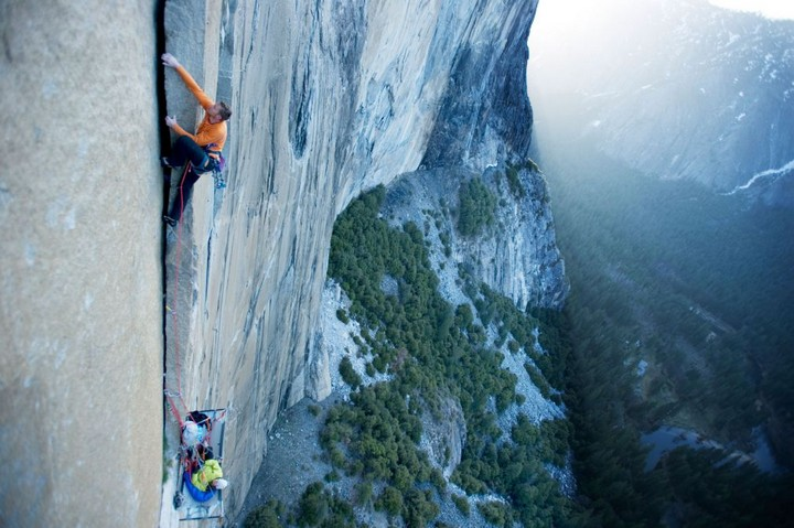 A woman belays on a portaledge while a man climbs on El Cap in Yosemite National Park, California.