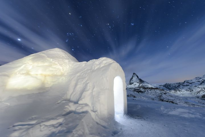 "The Jan. 28, 2016 long-time exposure photo shows an Igloo at the ""Igloo village"" (Iglu Dorf) in front of the famous Matterhorn mountain in Zermatt, Switzerland. The hotel-igloo village made of snow and ice at 2'815 meters about sea level with a bar, a restaurant, bedrooms and wellness celebrates its 20th anniversary. (Jean-Christophe Bott/Keystone via AP)"