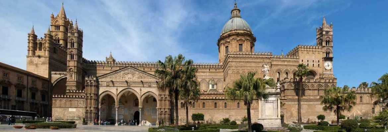 Prospetto laterale della cattedrale di Palermo con vista della cupola, della piazza, delle torri e dell'ingresso laterale.