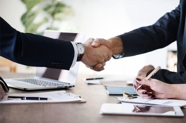 Business meeting handshake over table