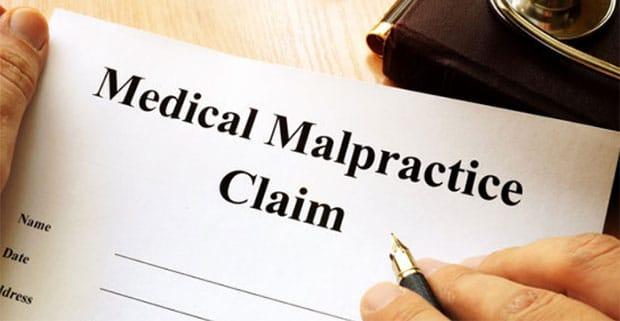 hand holding a Medical Malpractice Claim form