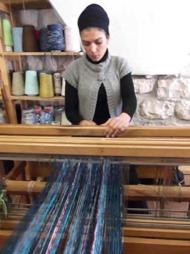 Liz Levy a weaver in Safed's Artists' Quarter weaves a scarf