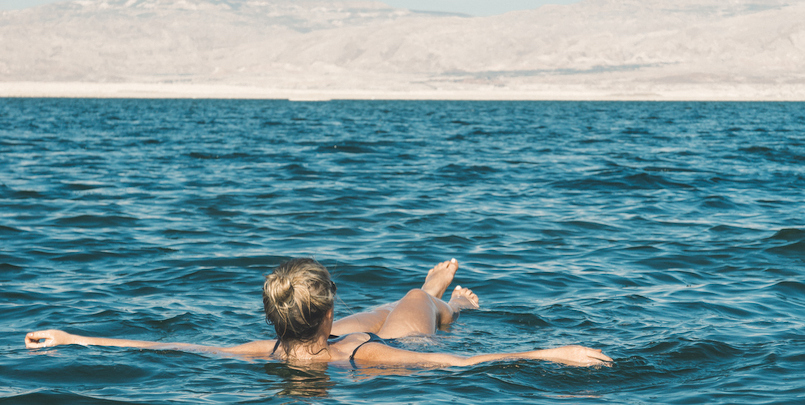 A woman floating in the salty water of the Dead Sea