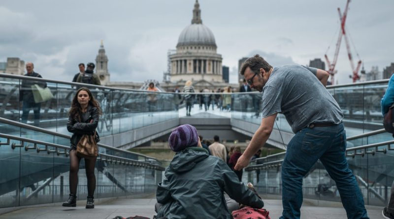 A man gives money to a homeless person with a young woman walking past.