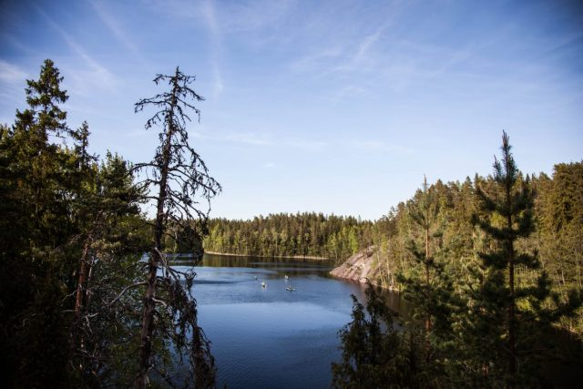 Deep blue lake with green hilly landscape at Nuuksio National Park