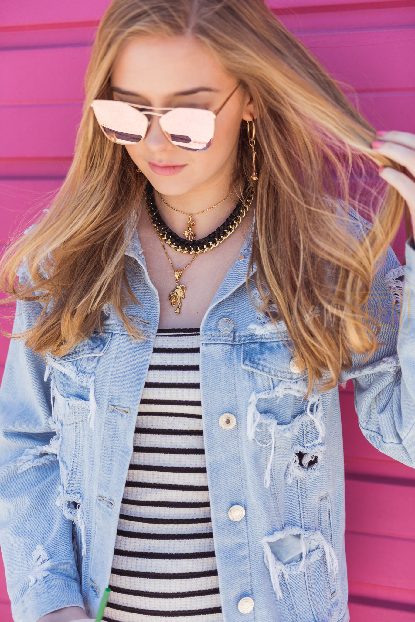 Hot Pink wall with teen wearing reflective shades, chokers, denim jacket and stirped tank