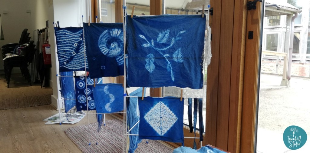 Display of shibori workshop pieces in the window of the Kingcombe Centre