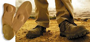 Pair of work boots standing at work site. - Copyright – Stock Photo / Register Mark