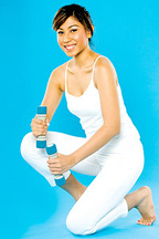 A woman posing in her exercise outfit and holding two dumbbells.