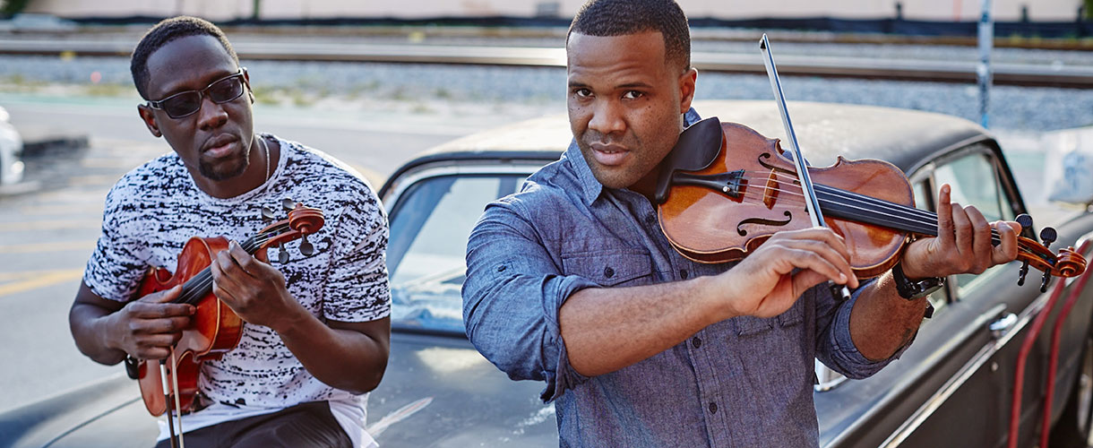 Kev Marcus and Wil B play violin on the hood of a car