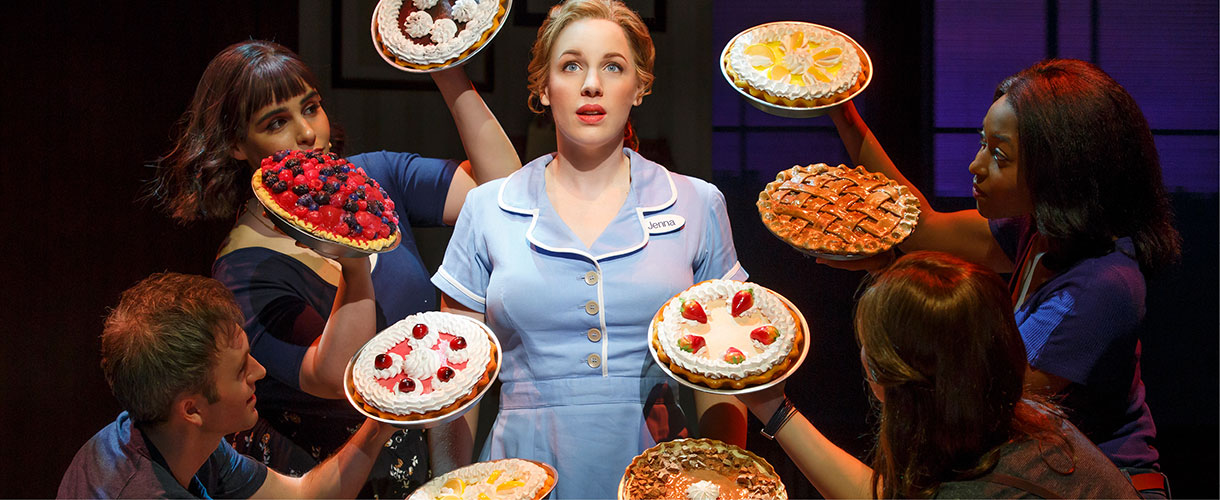 waitress Jenna stands surrounded by eight pies