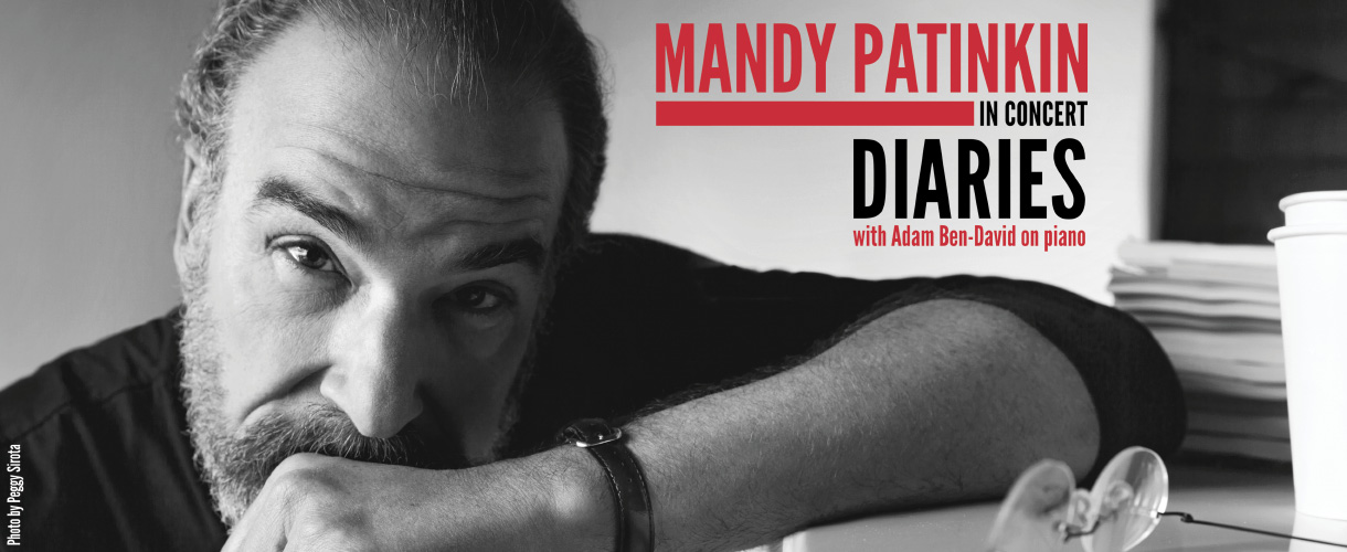 Mandy Patinkin stares straight ahead while leaning on a desk with left fist on his chin. Manuscripts, a coffee cup, and reading glasses surround the desk